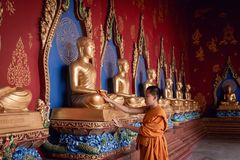Portrait of Little Novice Monk is Cleaning Statue of The Buddha in a Temple, Religion and Worship Concept.  stock images
