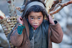 Portrait of little porter. GORKHA, NEPAL - NOVEMBER 29: Portrait of little porter with basket from village of Tibetan refuges on November 29, 2009 in Gorkha Stock Images