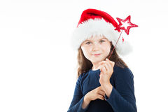 Portrait of a little pouting Christmas girl. Portrait of a little girl wearing a Christmas Hat, holding a red star. Isolated on white background Royalty Free Stock Photos