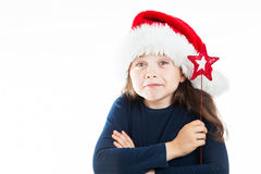 Portrait of a little pouting Christmas girl. Portrait of a little girl wearing a Christmas Hat, looking questioning, holding a red star. Isolated on white Stock Image