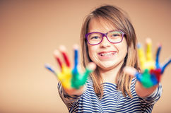 Portrait of a little pre-teen student girl showing painted hands. Toned Photo.  Royalty Free Stock Photos
