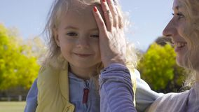 Portrait of little pretty blond caucasian girl sitting on her mother`s hands and smiling. Happy daughter resting with stock video footage