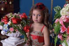 Portrait of a little princess girl in a red dress with flowers i stock image