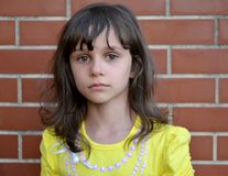 Portrait of the little sad girl against the background of a brick wall.  Stock Image