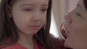 Portrait of a little sad girl with big eyes crying close up. Little kid is upset and unhappy. Concept of kids growing stock video footage