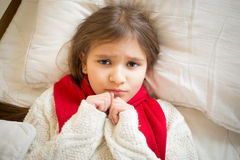 Portrait of little sad girl with flu lying in bed. Closeup portrait of little sad girl with flu lying in bed Royalty Free Stock Photography