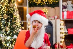 Portrait of little Santa child holding chocolate cookie and glass of milk. Santa Claus takes a cookie on Christmas Eve