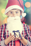 Portrait of a little Santa Claus holding a gift box Royalty Free Stock Image