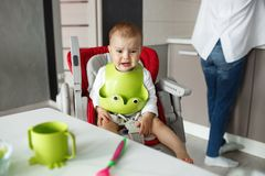 Portrait of little scared baby boy sitting in baby chair in kitchen, crying and screaming while mother cooking him food. Stock Photos
