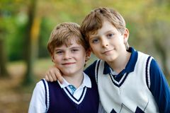 Portrait of little school kids boys sitting in forest. Happy children, best friends and siblings having fun on warm. Sunny day early autumn. Twins and family royalty free stock photos