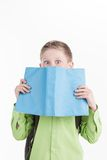 Portrait of little schoolboy with book on white background. Stock Image