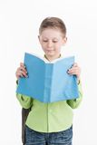Portrait of little schoolboy with book on white background. Royalty Free Stock Photo