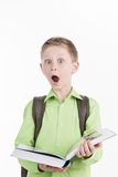 Portrait of little schoolboy with book on white background. Boy opened book and expressing shocking emotions Stock Photography