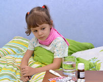 Portrait of the little sick girl sitting in a bed near drugs royalty free stock photography