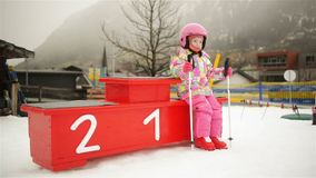 Portrait Of Little Ski Begginer. She Sitting On A Winners Podium. Cute Child Has A Lot Of Fun Spending Winter Vacation stock video footage