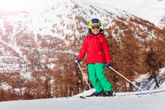 Portrait of little skier against mountain scene. Portrait of little skier with safety helmet, mask and poles posing against mountain scene stock images