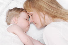 Portrait of little sleeping baby girl with her caring mother Stock Image