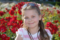 Portrait of the little smiling girl against red roses Stock Photography