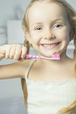 Portrait of little smiling girl brushing her teeth Royalty Free Stock Photo