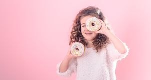 Portrait of a little smiling girl with donuts. Portrait of a little smiling girl with curly hair and two appetizing donuts in her hands, closes her eyes with royalty free stock images