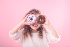 Portrait of a little smiling girl with donuts. Portrait of a little smiling girl with curly hair and two appetizing donuts in her hands, closes her eyes with stock photo