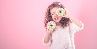 Portrait of a little smiling girl with donuts. Portrait of a little smiling girl with curly hair and two appetizing donuts in her hands, closes her eyes with stock image