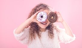 Portrait of a little smiling girl with donuts. Portrait of a little smiling girl with curly hair and two appetizing donuts in her hands, closes her eyes with royalty free stock photo