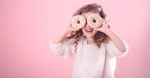 Portrait of a little smiling girl with donuts. Portrait of a little smiling girl with curly hair and two appetizing donuts in her hands, closes her eyes with royalty free stock image