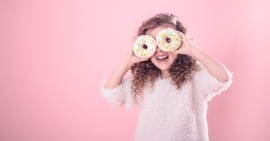 Portrait of a little smiling girl with donuts stock photo
