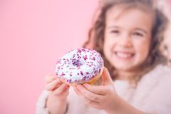 Portrait of a little smiling girl with donuts. Portrait of a little smiling girl with curly hair and appetizing donuts in her hands, on a pink background, a stock images