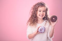 Portrait of a little smiling girl with donuts. Portrait of a little smiling girl with curly hair and appetizing donuts in her hands, on a pink background, a stock image