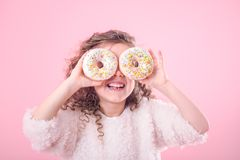 Portrait of a little smiling girl with donuts. Portrait of a little smiling girl with curly hair and two appetizing donuts in her hands, closes her eyes with royalty free stock photos