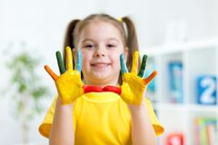 Portrait of little smiling girl with painted palms Stock Photos