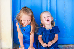 Portrait of Little smiling girls sitting near old Stock Photography