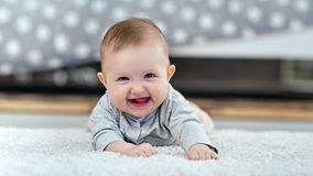 Portrait of little smiling toddler lying on fluffy carpet looking at camera in modern interior