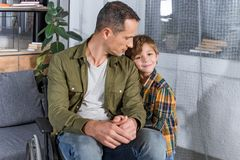 Portrait of little son and father in wheelchair. At home Royalty Free Stock Image