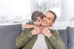 Portrait of little son hugging smiling father. At home royalty free stock photos