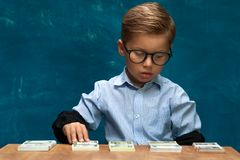 Little stylish boy counting money at workplace Royalty Free Stock Images