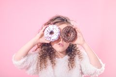 Portrait of a little surprised girl with donuts. Portrait of a little surprised girl with curly hair, and two mouth-watering donuts in her hands, closes her eyes stock photography
