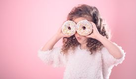 Portrait of a little surprised girl with donuts. Portrait of a little surprised girl with curly hair, and two mouth-watering donuts in her hands, closes her eyes royalty free stock photo