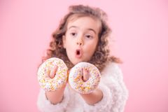 Portrait of a little surprised girl with donuts. Portrait of a little surprised girl with curly hair, and two mouth-watering donuts in her hands, closes her eyes royalty free stock image