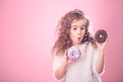 Portrait of a little surprised girl with donuts. Portrait of a little surprised girl with curly hair and two appetizing donuts in her hands, on a pink background royalty free stock images