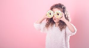 Portrait of a little surprised girl with donuts. Portrait of a little surprised girl with curly hair, and two mouth-watering donuts in her hands, closes her eyes stock photo