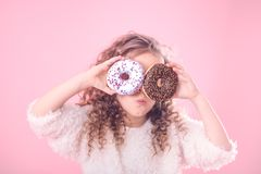 Portrait of a little surprised girl with donuts. Portrait of a little surprised girl with curly hair, and two mouth-watering donuts in her hands, closes her eyes royalty free stock photos