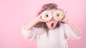 Portrait of a little surprised girl with donuts. Portrait of a little surprised girl with curly hair, and two mouth-watering donuts in her hands, closes her eyes stock image