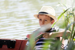 Portrait of a little sweet boy with a hat sitting on a boat and. Eating a watermelon. He likes to spend time by the river and enjoying a sunny day. Copy space Royalty Free Stock Photos