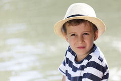 Portrait of a little sweet boy with a hat sitting next to the ri. Portrait of a cute little boy with a hat, sitting by the river and enjoy the beautiful and Stock Image