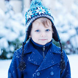 Portrait of little toddler boy in winter clothes with falling sn Stock Photography