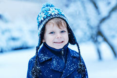 Portrait of little toddler boy in winter clothes with falling sn Stock Image