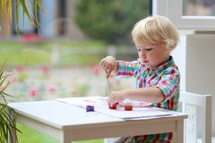 Portrait of little toddler girl painting with brush Stock Image